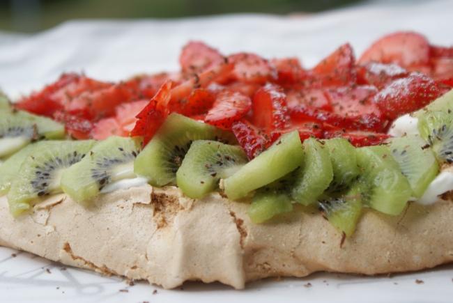 Pavlova med jorgubbar, kiwi och vispgrädde. Pavlova with whipped cream, strawberries and kiwi. Mansikoilla, kivihedlemillä ja kermavaahdolla koristettu Pavlova.