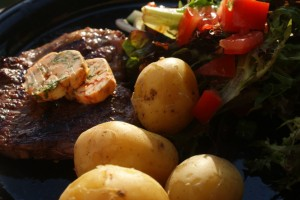 Kött, kryddsmör, potatis och sallad. Meat, flavored butter, potatoes and sallad. Lihaa, maustevoita, perunoita ja salaattia.